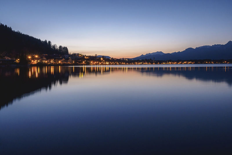 Illuminated town reflecting in lake hopfen against clear sky at dusk