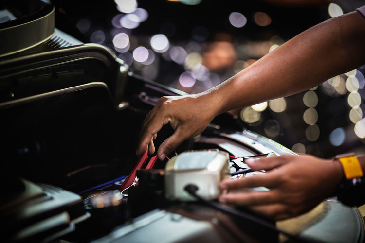 Cropped hands of person repairing car