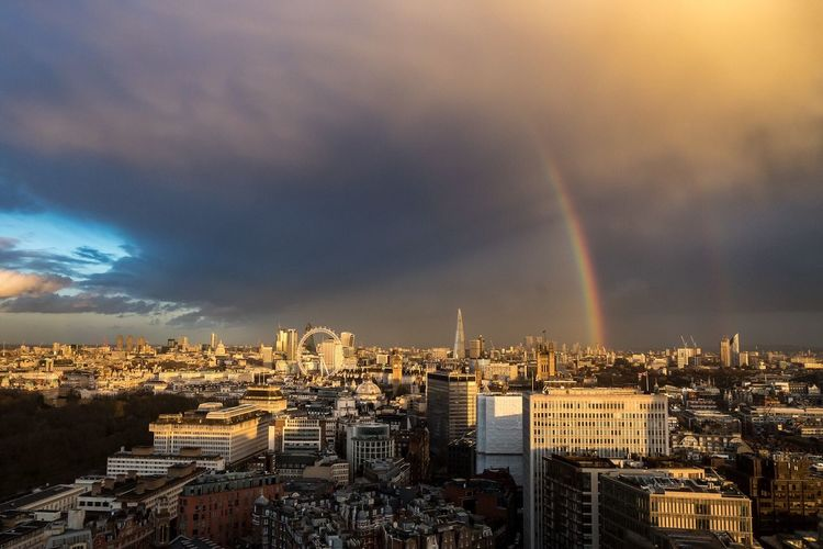 Scenic View Of Rainbow Over Cityscape Against Sky During Sunset