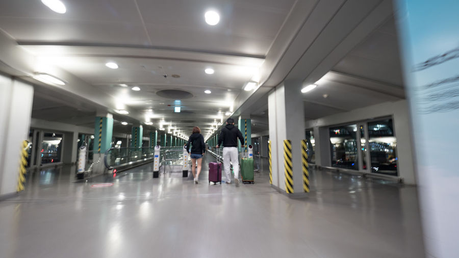 People with luggage walking on the moving walkway at the airport terminal of Seoul, South Korea Airport Architecture Baggage Escalator Hallway Horizontal Indoors  Luggage Modern Passenger People Ride Seoul South Korea Suitcase Terminal Tourist Travel Travelator Walkway