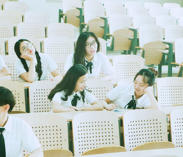 Students wearing uniforms while sitting in classroom