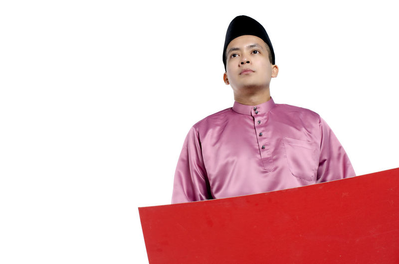 Portrait of young and handsome asian man with traditional clothing holding red cardboard White Background Studio Shot Front View One Person Indoors  Young Men Young Adult Copy Space Looking Cut Out Leisure Activity Looking Away Standing Red Men Waist Up Occupation Contemplation Purple