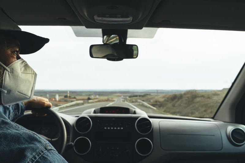 Man seen through car windshield