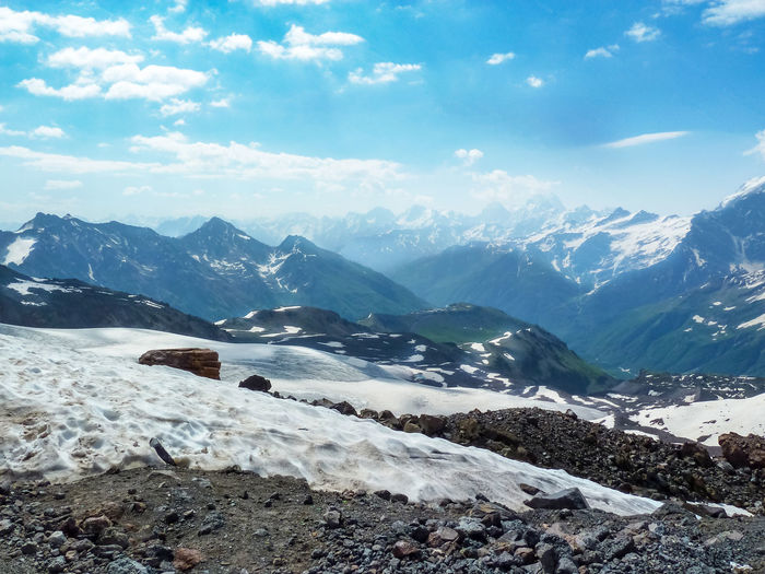 Snowy mountain landscape of Elbrus on a Sunny summer day. Glaciers and rocks. Cold Temperature Mountain Scenics - Nature Snow Tranquil Scene Beauty In Nature Cloud - Sky Environment Landscape Nature Snowcapped Mountain Tranquility Sky Non-urban Scene No People Range Mountain Peak Solid Rock Mountain Range Caucasus Mountains Hiking Ice Panoramic Clouds And Sky