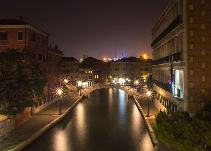 Illuminated canal in venice at night