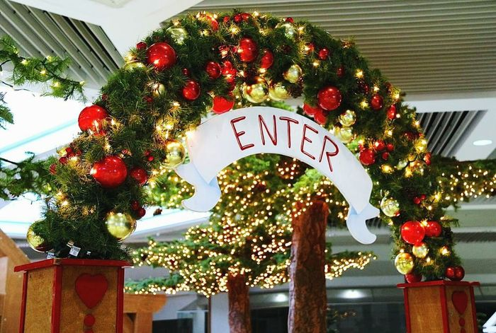 The Entrance to Santa's Wonderland. Enter Sign Red White Evergreen White Lights  White Sign Red Letters Christmas Around The World Enter Sign Holidays Cover Art Cover Photo Holiday Decorations Holiday Decor Christmas Decorations Christmas Decor Ceiling Design Indoor Trees Holiday Lighting Holiday Lights Entrance Gate Entrances