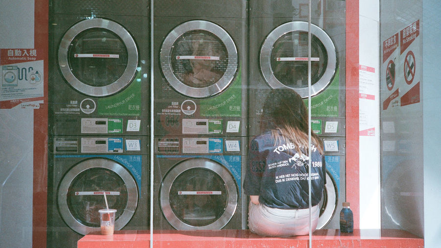 Glass - Material Reflection Window Transparent Women One Person Real People Text Day Lifestyles Building Exterior Communication Machinery Circle Store Geometric Shape Architecture Washing Machine Outdoors Laundromat