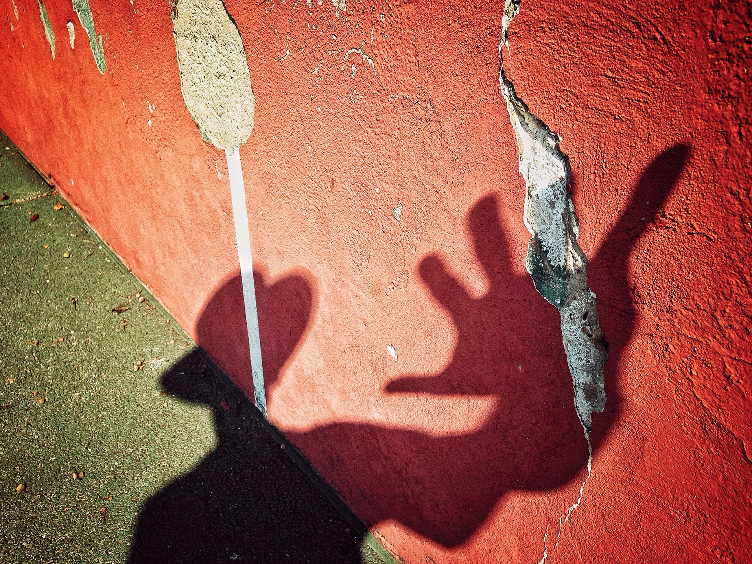 shadow, wall - building feature, red, high angle view, textured, art, creativity, street, focus on shadow, art and craft, graffiti, close-up, heart shape, sunlight, wall, outdoors, day, paint, pattern, human representation