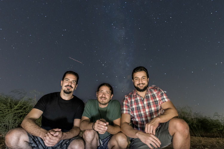 Portrait of smiling friends sitting on cliff against starry sky at night