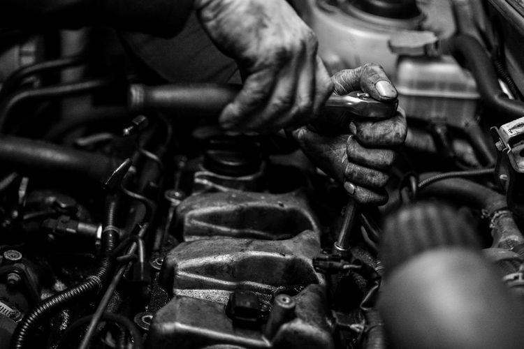 Cropped Hands Of Manual Worker Repairing Engine