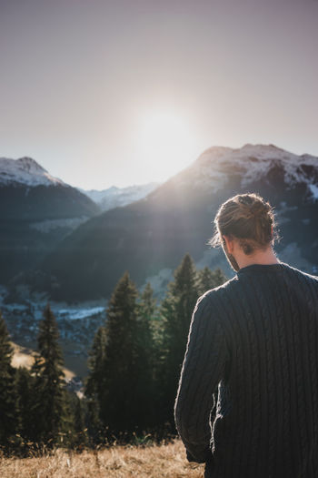Enjoying the mountain view Adventure Beauty In Nature Clear Sky Cold Temperature Day Leisure Activity Lifestyles Live Authentic Men Mountain Mountain Range Nature One Person Outdoors People Real People Rear View Scenics Sky Standing Sunlight Tranquility Tree Warm Clothing Young Adult