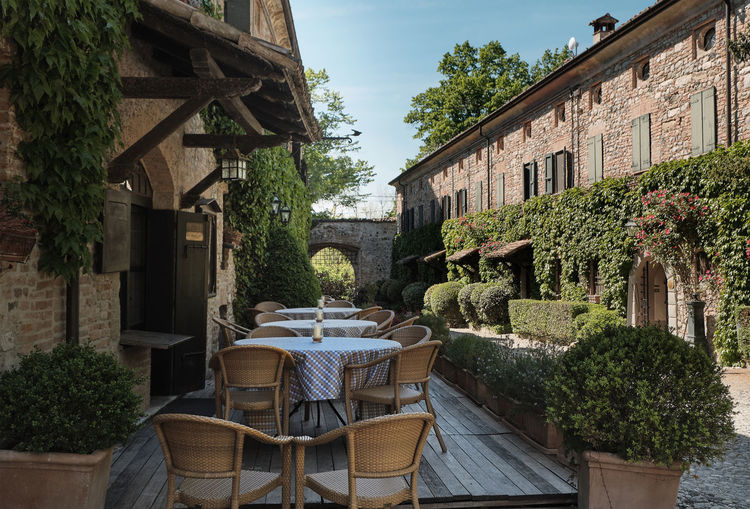 April 2019 PIACENZA ITALY - table and chairs of restaurants in front of historic ancient medieval village of Rivalta Castle - italian relax and style life - Piacenza - Emilia Romagna, Italy Brick Wall Table For Two Wood Brown Nobody Wall Wooden Comfortable Still Life Rustic Idyllic Building Exterior Old Luxury Historic Tranquil Scene Wine Diner Tablecloth Restaurant Dining Table Outdoors Fine Dining Romantic Horizontal Table Chair Door Lifestyle Plant Image Rundown Italy Scene Culture Exterior Vertical Bush Bistro Outdoor Clean Fence Tranquil Façade Traditional Italian Group Staircase Day Elégance