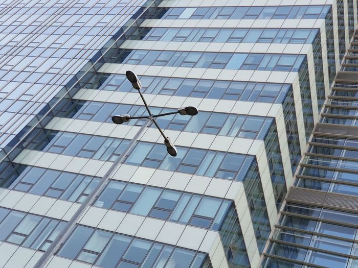 Streetlight Streetlamp Glass Flying Tall - High Reflection Skyscraper Outdoors Full Frame Window Glass - Material Day No People City Office Modern Office Building Exterior Building Low Angle View Building Exterior Architecture 17.62°