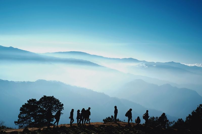 Silhouette people on mountain range against sky