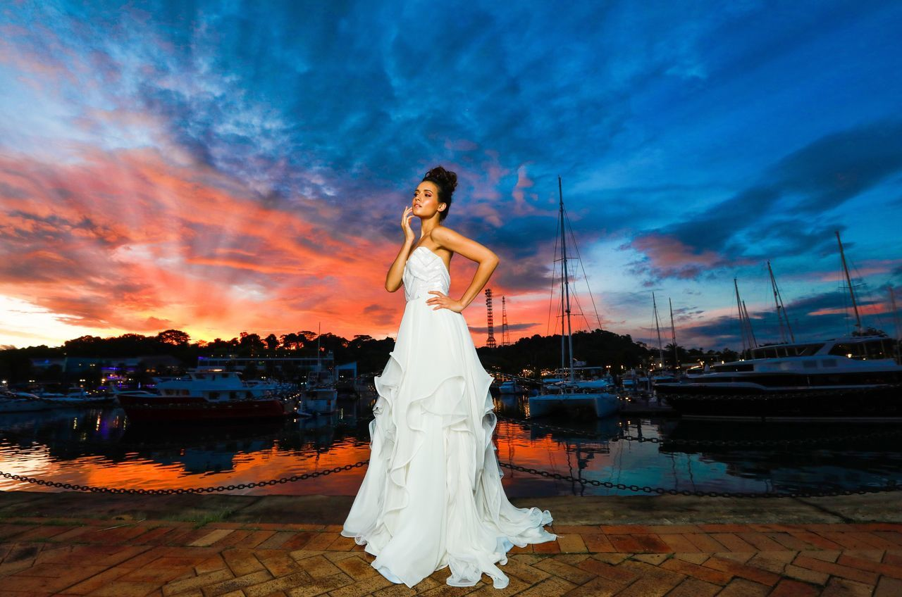 cloud - sky, sunset, full length, beautiful woman, sky, beauty, outdoors, water, one person, beautiful people, young adult, real people, women, adult, beach, sea, standing, portrait, lifestyles, nautical vessel, young women, one woman only, fashion model, beauty in nature, nature, only women, night, wedding dress, one young woman only, adults only, bride, people