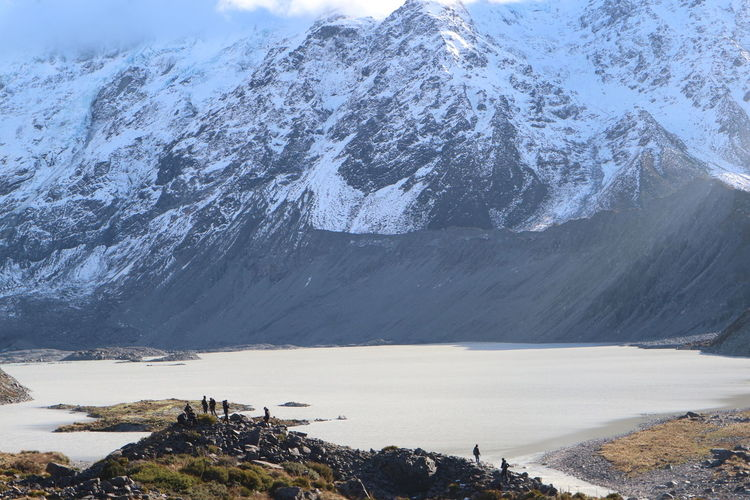 Scenic view of lake by mountain during winter