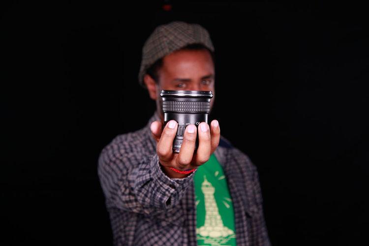 Close-Up Portrait Of Man Holding Lens Against Black Background