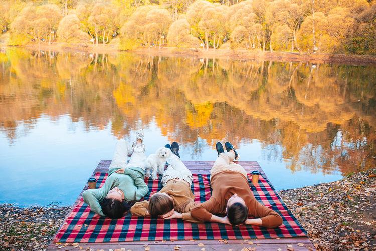 People sitting by lake