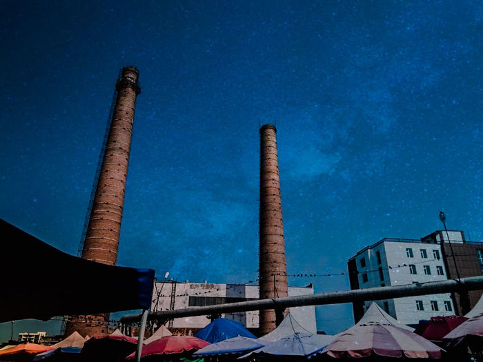 Low angle view of factory against blue sky