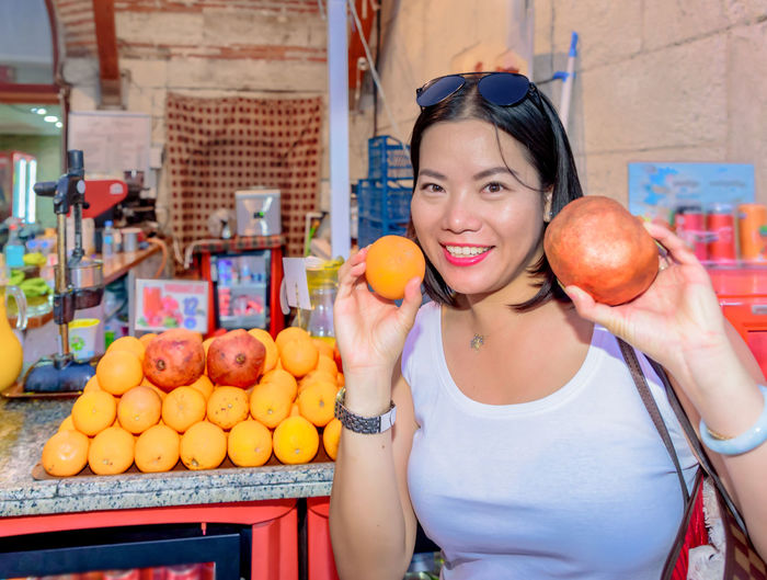 Portrait of smiling woman holding fruits while standing in market