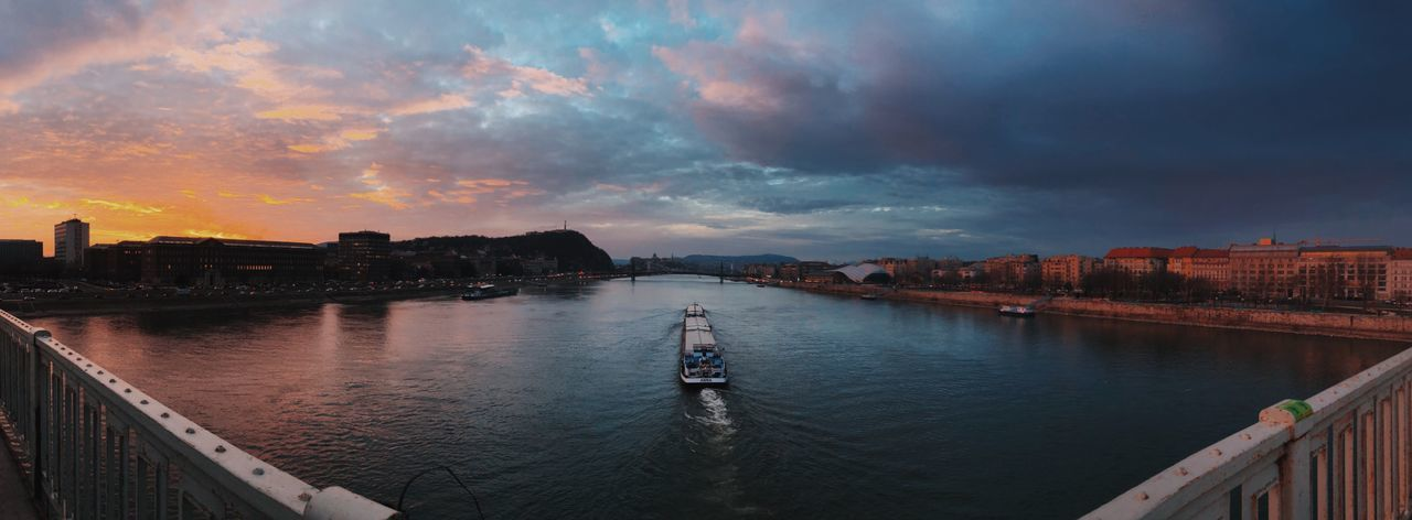 Panoramic view of river against cloudy sky at sunset