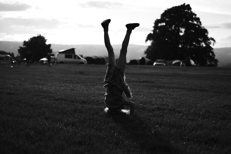Field Real People One Person Lifestyles Leisure Activity Men Grass Upside Down Handstand  Outdoors Day Tree Full Length Nature Sky People