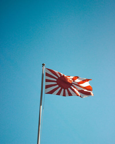 Low angle view of flag against clear blue sky