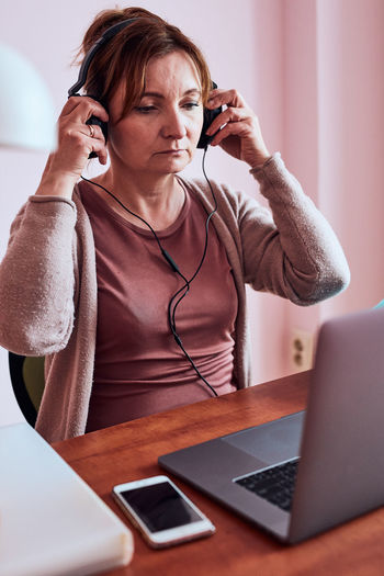Woman working talking doing her job remotely during video chat phone call on laptop from home