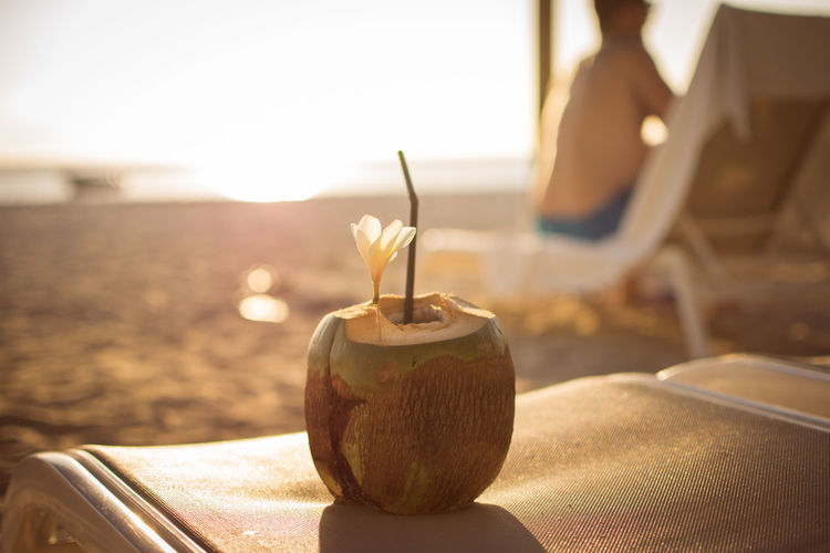 Close-up of coconut on lounge chair at beach during sunset