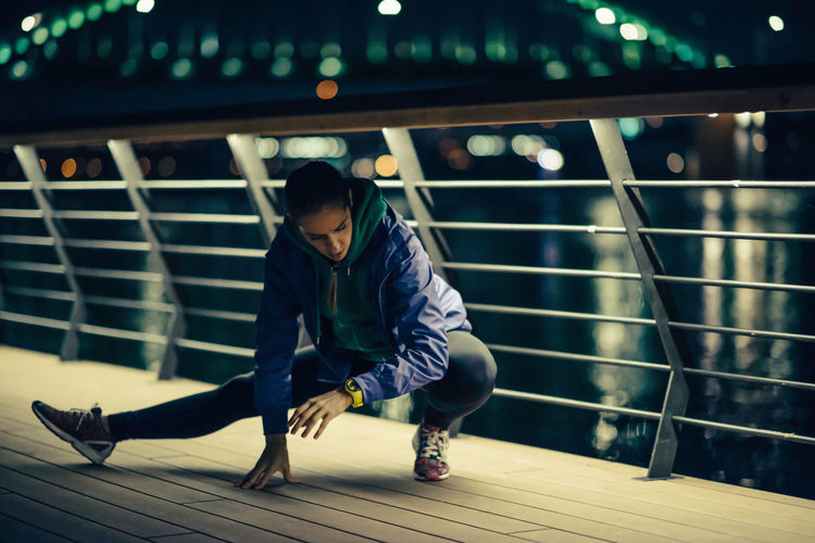 Full length of woman exercising by railing at night