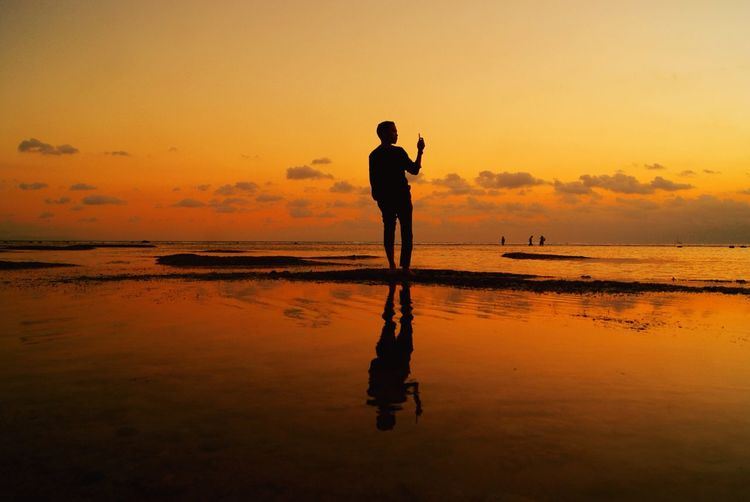 Beuauty of Sunset from Lombok Sunset Silhouette Water Sea Full Length Nature Real People One Person Reflection Standing Beach Sky Scenics Beauty In Nature Tranquil Scene Lifestyles Tranquility Leisure Activity Men Outdoors First Eyeem Photo Neon Life
