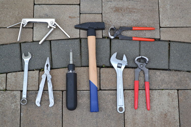 High Angle View Of Work Tools On Paved Street