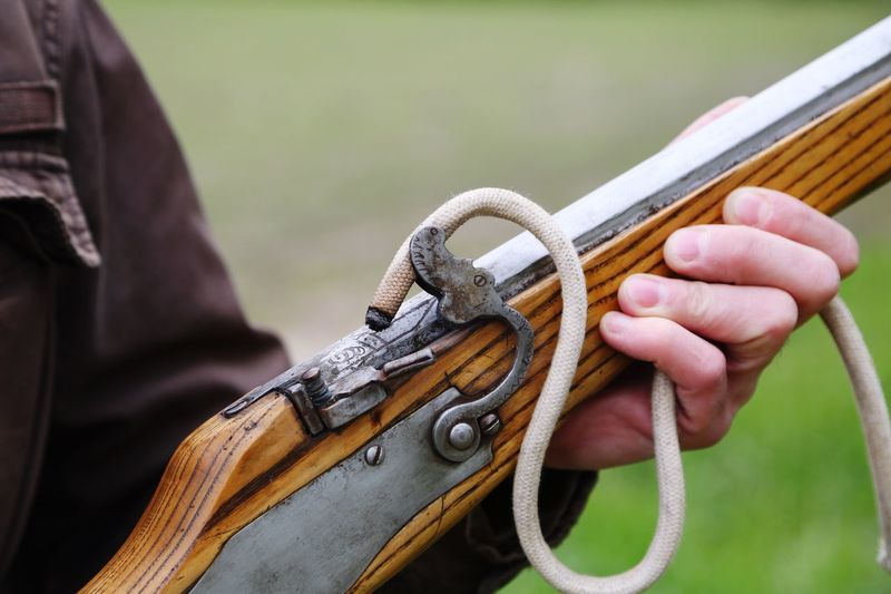Close-Up Midsection Of Man Holding Old Rifle
