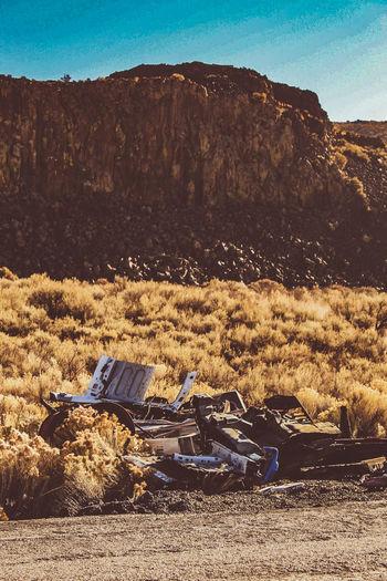 Abandoned car on land against sky