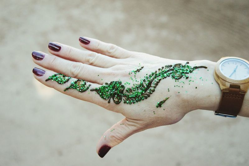 Cropped hand of woman with henna tattoo