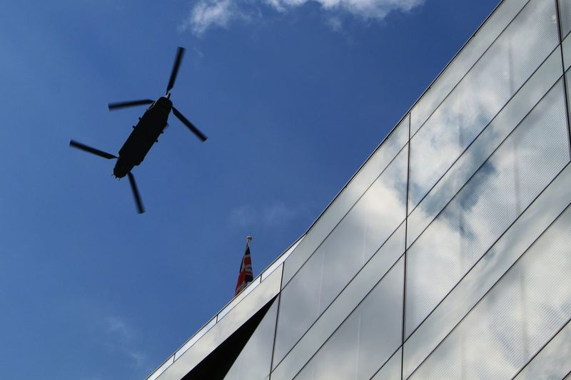 Low Angle View Of Military Helicopter Over Building Against Sky
