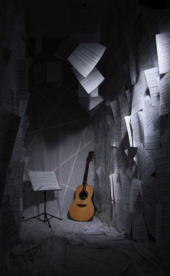 Guitar and sheet music in darkroom