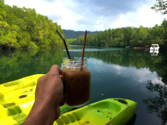 Midsection of person holding drink by lake