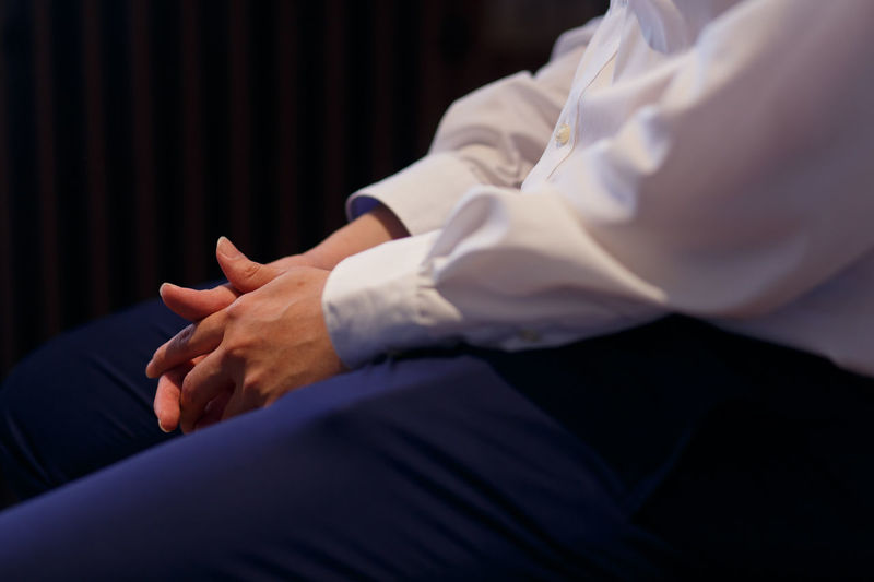 Midsection man in a suit sits and cross-fingers in the dark room Indoors  Men Midsection Hand Human Hand People Human Body Part Adult Occupation Males  Real People Side View Mid Adult Clothing Holding Hands Expertise Cross Fingers Thinking Business Finance And Industry Casual Clothing Long Sleeve Shirt Fashion Darkroom