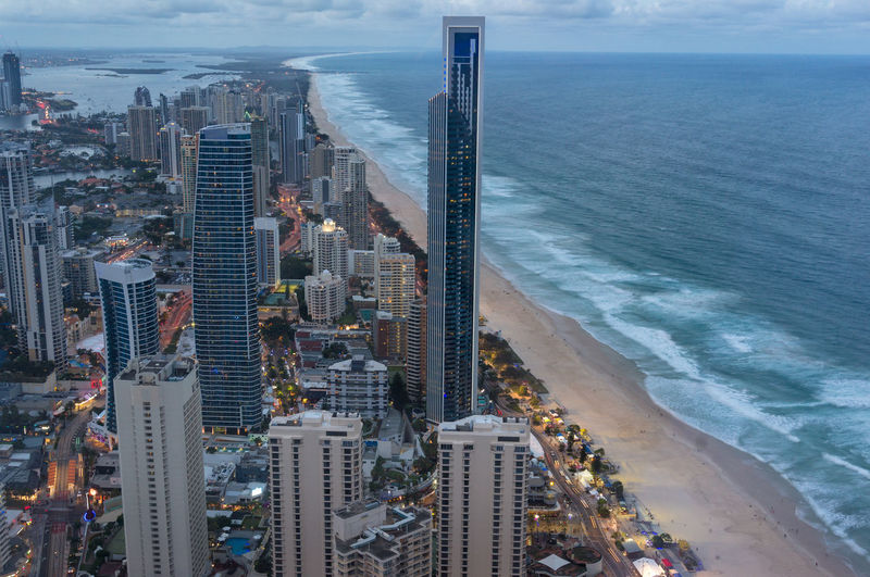 Aerial cityscape of modern city with skysrapers and tall office buildings along the ocean coastline