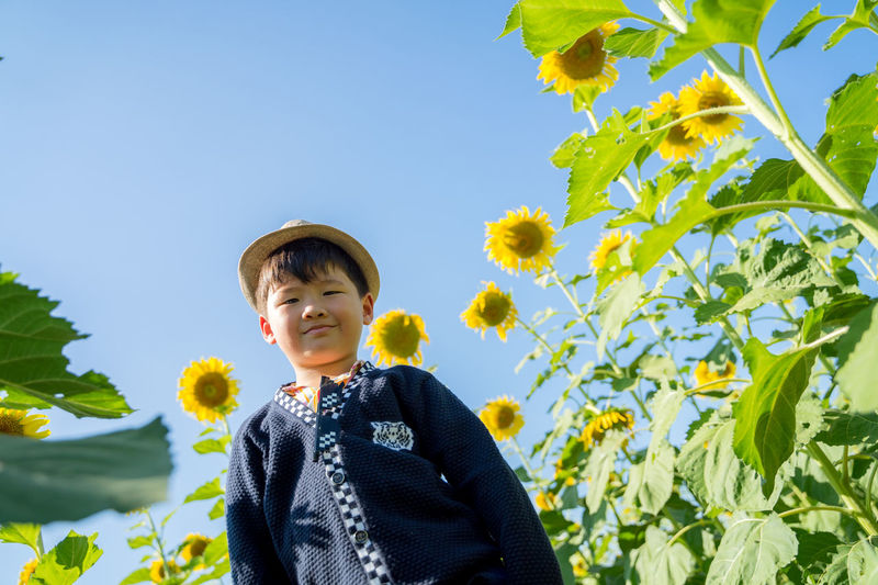 Portrait of smiling woman standing on yellow flowering plants against sky