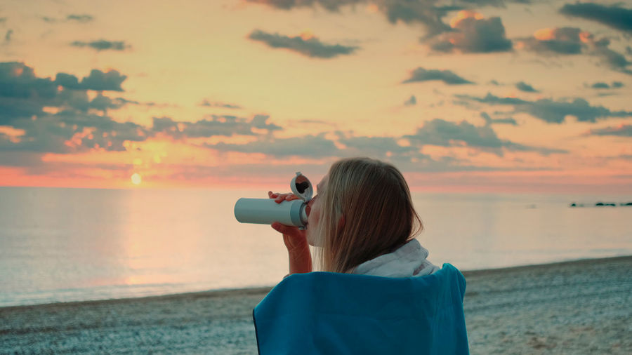 Rear view of woman photographing sea against sky during sunset