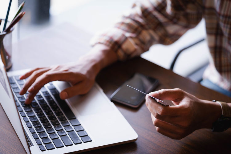 Midsection of man holding credit card and using laptop on table