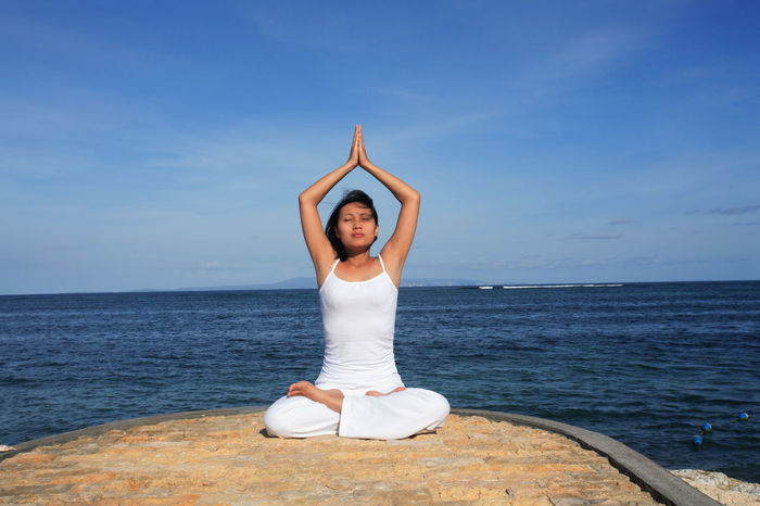 Adult Beach Blue Cross-legged Eyes Closed  Healthy Lifestyle Human Arm Human Body Part Lifestyles Limb Meditating One Person Outdoors Praying Relaxation Relaxation Exercise Sand Sea Sky Spirituality The Human Body Vacations Women Yoga Zen-like