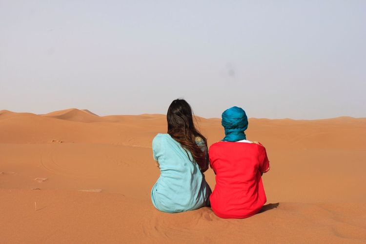 EyeEmNewHere Rear View Arid Climate Desert Sand Two People Real People Togetherness Sand Dune Sitting Landscape Women Scenics Day Nature Leisure Activity Clear Sky Lifestyles Beauty In Nature Outdoors Sky