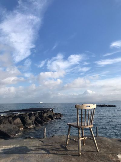 Deck chairs on rocks by sea against sky