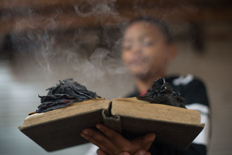 Close-Up Of Boy Holding Burning Book