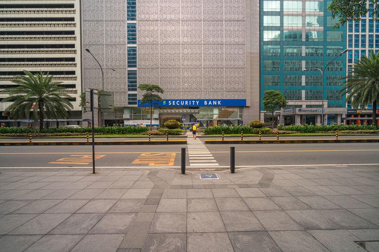 Person walking on sidewalk by modern building in city