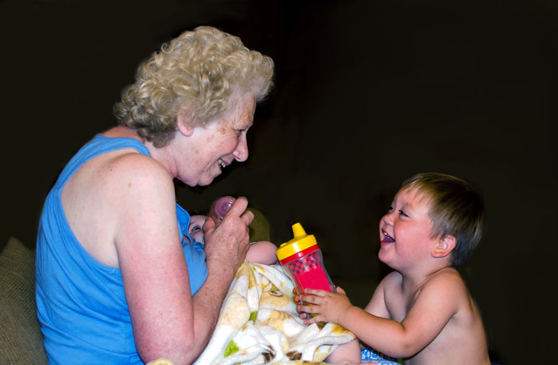 Grandmother laughs at her little grandson as she feeds his baby sister a bottle