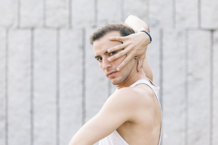 Portrait of young man dancing against wall